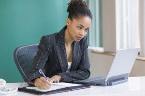 Businesswoman taking notes at her desk