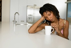 Bored Young Woman Stirring Coffee